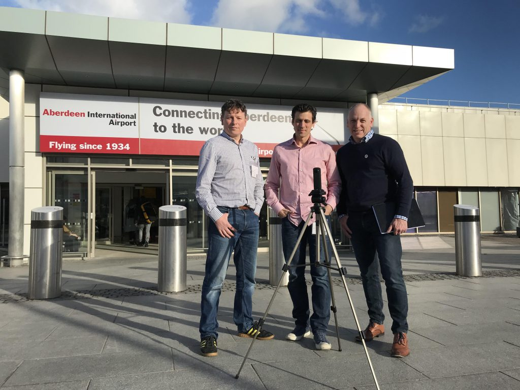 3 men standing outside Aberdeen Airport